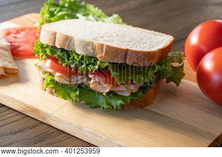 Fresh Turkey, Lettuce And Tomato Sandwich On Cutting Board