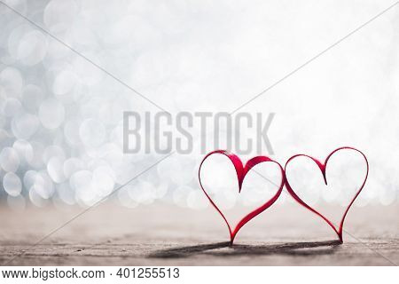 Two red ribbon hearts on glitter background with copy space for text, Valentines day concept