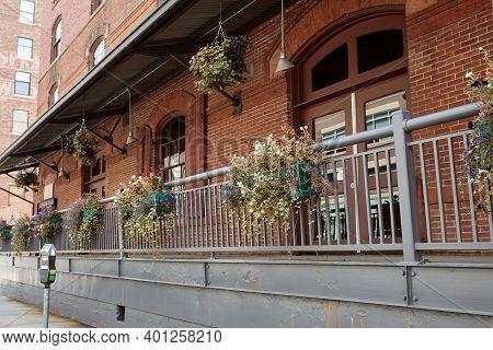 Brick Facade Of Building With Flower Pots On Railing In Downtown Denver.  Denver, Colorado, Usa