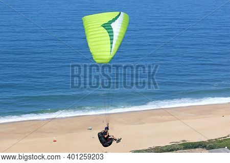 Paraglider Flying His Wing Above The Beach