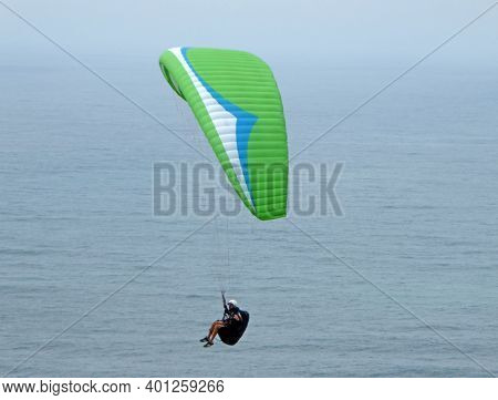 Paraglider Flying Green Wing Above The Sea