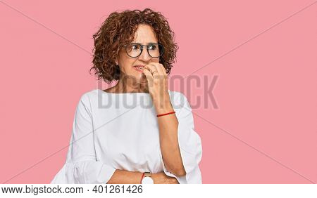 Beautiful middle age mature woman wearing casual clothes and glasses looking stressed and nervous with hands on mouth biting nails. anxiety problem.