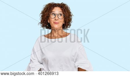 Beautiful middle age mature woman wearing casual clothes and glasses smiling looking to the side and staring away thinking.