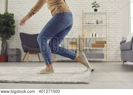 Clumsy Woman Trips Over The Rug In The Living-room And Is About To Fall On The Floor