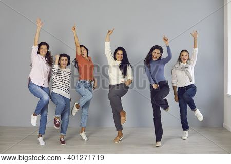 Group Of Happy Young Women Jumping For Joy And Laughing, Celebrating Team Success