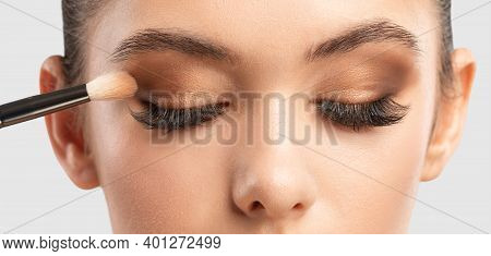 Portrait Of A Charming Brunette Woman With Healthy Clean Skin. Makeup Artist Applies Eye Shadow.the