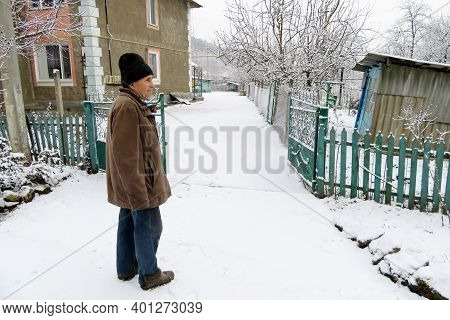 Elderly Man Standing On The Rural Street Near The Iron Gates And House During A Snowfall. Concept Of
