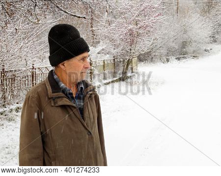 Elderly Man Standing On The Rural Street During A Snowfall. Concept Of Cold Weather, Snow Winter, Ho