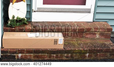 A Package Is Delivered To A Residential House Left Out In The Open To Be Stolen In December.