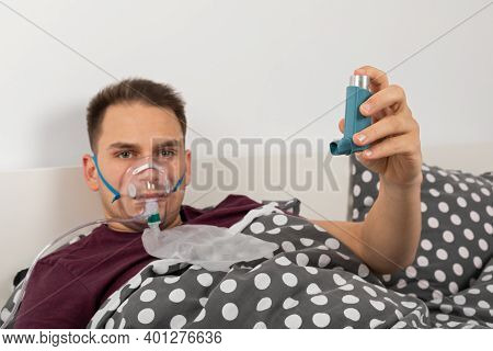 Male Patient With Oxygen Mask At Home Is Lying In Bed, Holding An Inhaler Spray With Salbutamol