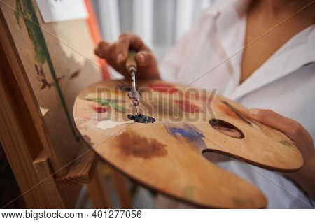 A Palette Knife With Oil Paint On Female Hand On The Background Of Palette