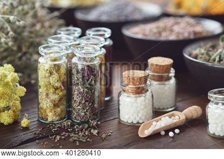Three Bottles Of Homeopathic Globules, Bottles Of Dried Medicinal Herbs, Bowls And Bunches Of Herbs