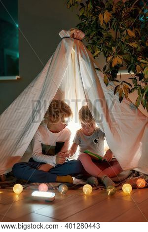 Cozy House. Two Little Siblings, Boy And Girl Reading A Book Together While Sitting On A Blanket In