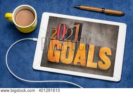 2021 goals - New Year resolutions concept - word abstract in vintage letterpress wood type blocks on a digital tablet with coffee