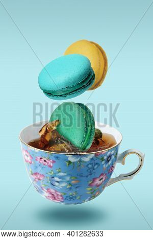Color French Macaroons Falling In To The Decorated Blue Porcelain Teacup Full Of Tea