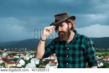Brutal Caucasian Hipster With Moustache On Cloudy Sky Background. Male Brutal Beauty. Confident West