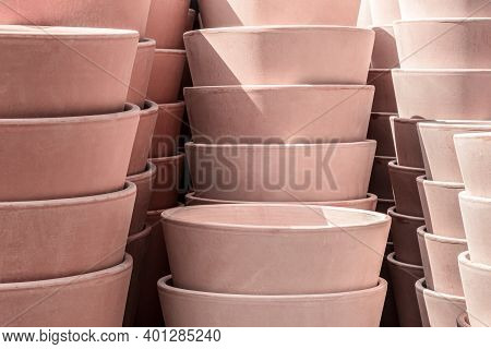 Pink Clay Flowerpots In Sunlight, Stacked On Top Of Each Other.