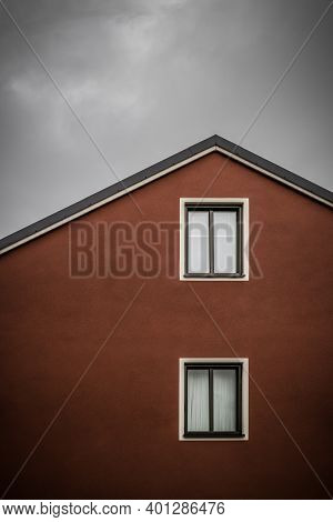 Red House With White Windows Against Dark Cloudy Sky.