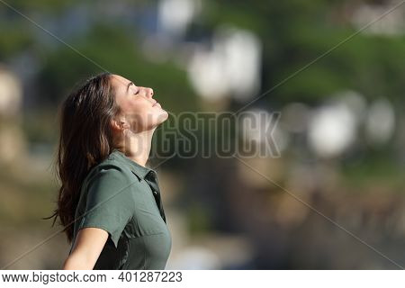 Profile Of A Woman Breathing Fresh Air Outdoors In A Mountain Town