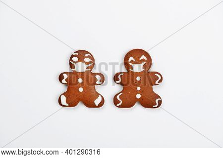 The Hand-made Eatable Gingerbread Little Men With Face Masks On White Background