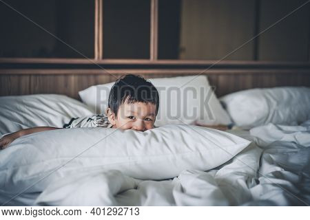 2 Years Old Little Boy Dressed In Striped Tshirt Are Relaxing And Lying Down In Bed, Warm And Cozy B