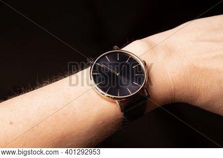 Women's Hand, Wrist With Quartz Wrist Watch With Golden Hands, On Black Background