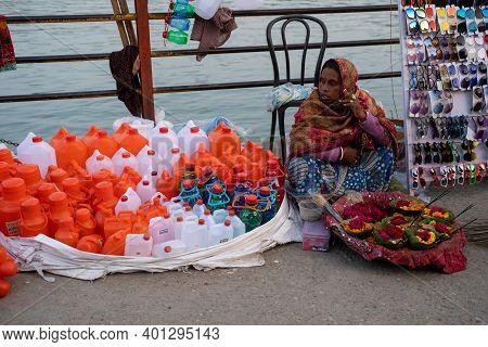 Haridwar, India - Feburary 22, 2020: Indian Woman Selling Plastic Jugs For Collection Of Holy Water