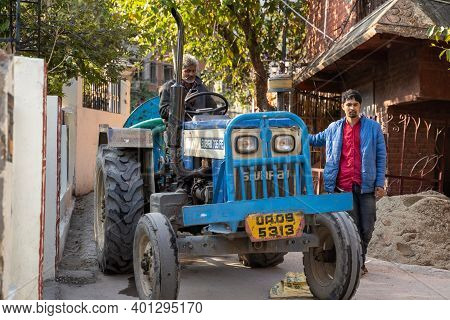 Rishikesh, India - Feburary 22, 2020: Two Indian Men Guide A Tractor Through The Narrow Streets Of T