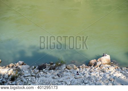 Rishikesh, India - Feburary 22, 2020: Two Indian Men Sit On A Large Rock On The Riverbank Shores Of