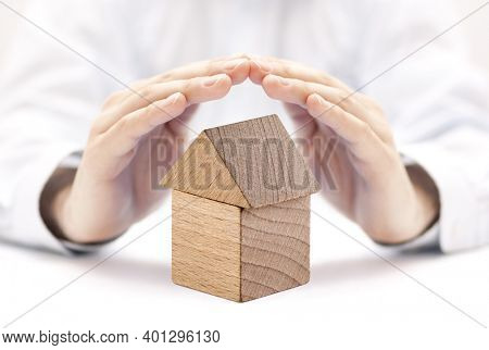 Small wooden house protected by hands. Home insurance concept