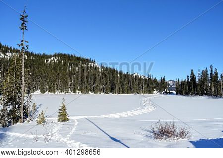 A Scenic Winter Landscape View Of Cross Country Skii Trackers On Top Of A Frozen Lake Covered In Sno
