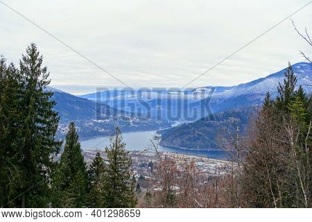 A Faraway View Looking Down On The Town Of Nelson During The Winter With Lake Kootenay In The Backgr