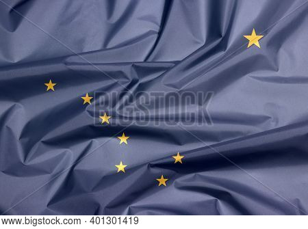 Fabric Flag Of Alaska. Crease Of Alaska Flag Background, The States Of America, Eight Gold Stars, In