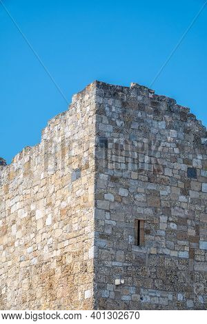 Ruins Of The Fortress Wall Against The Blue Sky. Ancient Historic Genoese Castle Or Fortress Against