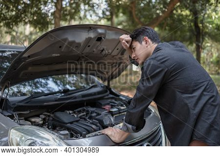 Man' Hand Open Hood Of A Broken Car And Wipe The Sweat On The Road In The Forest. Car Breakdown Conc