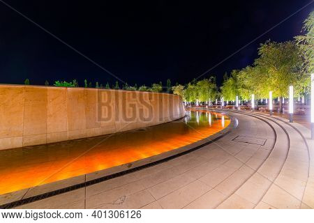 Walking Path Around Fountain In Resort With Colored Light Illumination And Trees On Side At Evening.