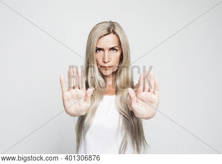 Lifestyle and emotion concept: Senior grey-haired woman doing stop sign with serious and confident expression over grey background
