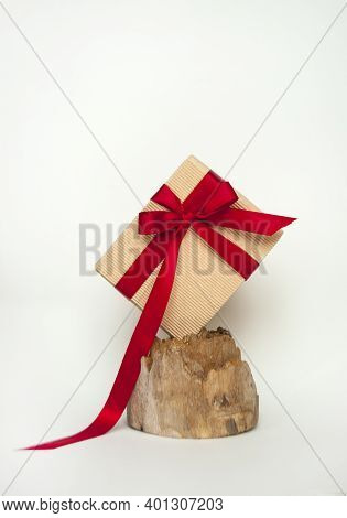 Giftbox Wrapped In Craft Paper Bowed With Red Ribbon On A Beautiful Wooden Stump.