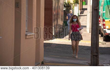 Brazilian woman. Blonde girl walking on the sidewalk. Woman with red blouse wearing mask. Girl walki