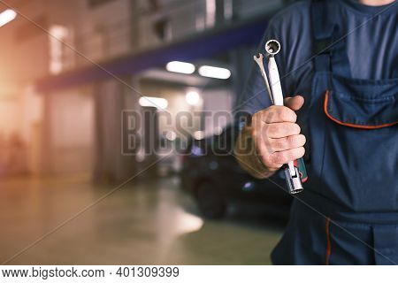 The Hand Of A Car Repairman With Keys And A Special Tool On The Background Of The Service Area. A Me