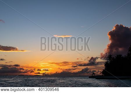 Dramatic Sunset Over The Indian Ocean On Vilamendhoo Island In Maldives, With Cumulonimbus Clouds An