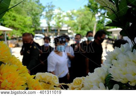 Blurred Images Of Masked Men Attending Religious Ceremonies To Pray For Deceased At Cremation During