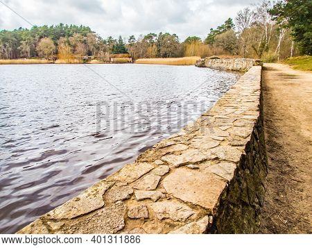Frensham Little Pond, Surrey, England United Kingdom. The Retraining Stone Wall.