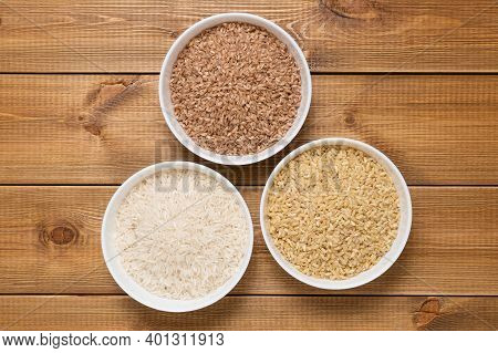 Raw Uncooked Rice In White Ceramic Bowls On Wooden Table, Top View. Brown, Red And White Long Basmat