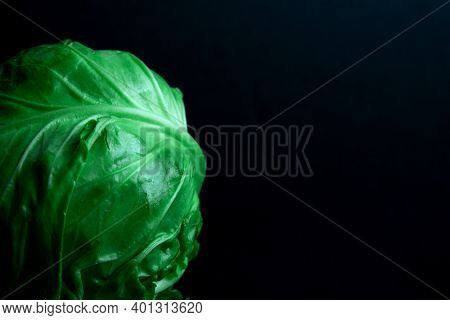 Ripe Solid Roach Of Green Cabbage On A Black Background With Copy Space