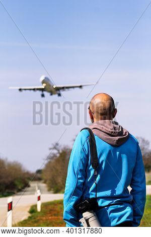 Man Is Spotting Airplane. Spotting Airplane. Man Is Looking At The Plane Which Is Landing. Aircraft