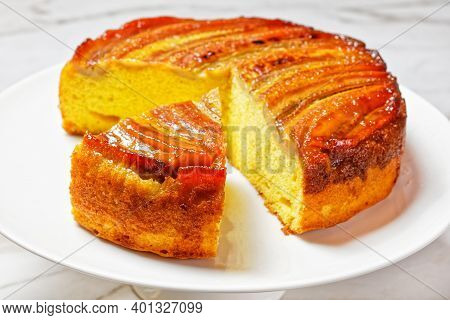 Upside Down Banana Cake On A White Plate On A Marble Table, Horizontal View From Above, Close-up