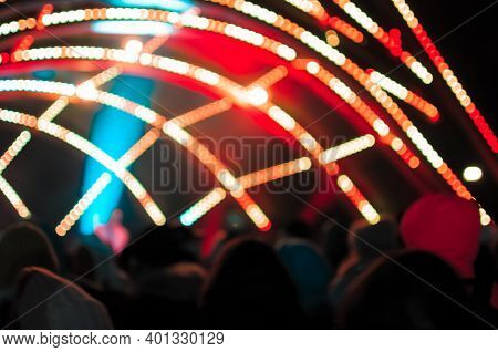 Blurred Bokeh Light On A Dark Background. Defocused Image Of An Illuminated Outdoor Stage Area At Ni