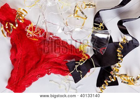 After the office party concept photo of red knickers, a bow tie and champagne glasses on a table.