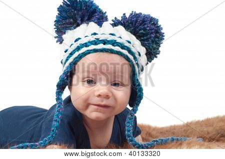 Cute baby in knitted hat with big pom-pons